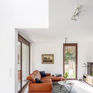 Offenes Modernes Wohnzimmer mit weißer Wandfarbe, Betonboden, freistehendem TV und grauem Boden in Sonstige