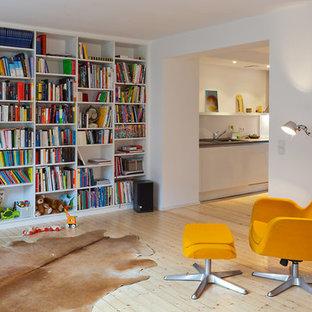 Imagen de sala de estar con biblioteca abierta, contemporánea, de tamaño medio, sin chimenea y televisor, con paredes blancas y suelo de madera clara