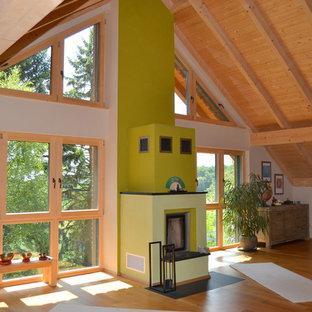 Foto di un ampio soggiorno tropicale aperto con libreria, pareti bianche, parquet chiaro, stufa a legna, cornice del camino in cemento, nessuna TV e pavimento beige