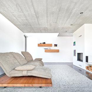 Abgetrenntes Modernes Wohnzimmer mit Kamin, verputzter Kaminumrandung, weißer Wandfarbe, Wand-TV und grauem Boden in Stuttgart