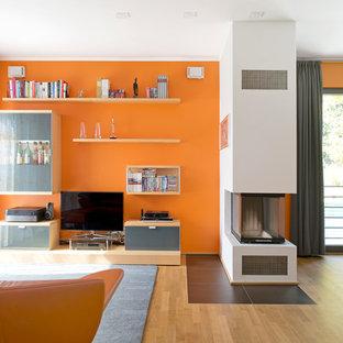 Aménagement d'une salle de séjour contemporaine de taille moyenne et ouverte avec un mur orange, un sol en bois clair, une cheminée double-face, un manteau de cheminée en béton et un téléviseur encastré.