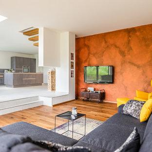 Mittelgroßes, Offenes Modernes Wohnzimmer mit weißer Wandfarbe, braunem Holzboden, Wand-TV und braunem Boden in Sonstige