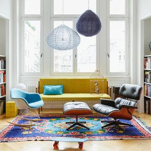 Modelo de sala de estar con biblioteca cerrada, ecléctica, de tamaño medio, con paredes blancas, suelo de madera clara y suelo beige
