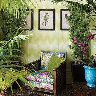 Immagine di un soggiorno tropicale di medie dimensioni e aperto con sala formale, pareti verdi, pavimento in legno massello medio, nessun camino e nessuna TV