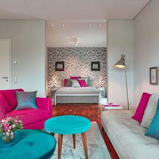 Mittelgroßes, Repräsentatives, Fernseherloses, Offenes Modernes Wohnzimmer ohne Kamin mit grauer Wandfarbe, braunem Holzboden und braunem Boden in Berlin
