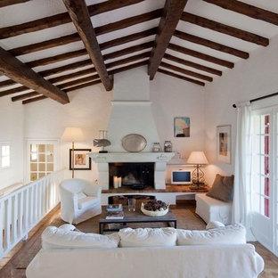 Cette photo montre un salon mansardé ou avec mezzanine montagne de taille moyenne avec une salle de réception, un mur blanc, une cheminée standard et un manteau de cheminée en pierre.