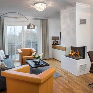 Kleines, Fernseherloses, Abgetrenntes Modernes Wohnzimmer mit weißer Wandfarbe, braunem Holzboden, Tunnelkamin, verputzter Kaminumrandung und braunem Boden in Sonstige