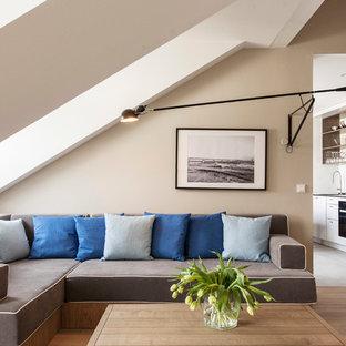 Modernes Wohnzimmer mit beiger Wandfarbe, hellem Holzboden und beigem Boden in Berlin