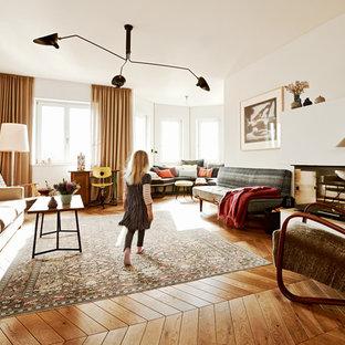 Foto de sala de estar cerrada, contemporánea, extra grande, sin televisor, con paredes blancas, suelo de madera en tonos medios, chimenea de esquina y marco de chimenea de yeso
