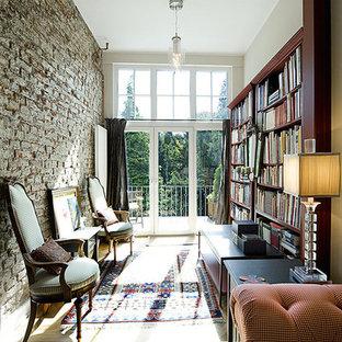 Imagen de sala de estar con biblioteca cerrada, tradicional, pequeña, sin chimenea y televisor, con suelo de madera clara y paredes beige
