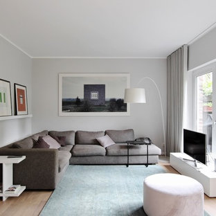 Design ideas for a small contemporary enclosed family room in Dusseldorf with grey walls, medium hardwood floors, no fireplace, a freestanding tv and brown floor.