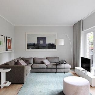 Kleines, Abgetrenntes Modernes Wohnzimmer ohne Kamin mit grauer Wandfarbe, braunem Holzboden, freistehendem TV und braunem Boden in Düsseldorf