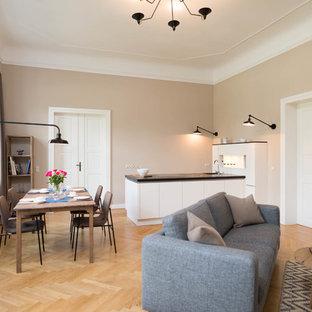 Mittelgroßes, Fernseherloses, Offenes Modernes Wohnzimmer ohne Kamin mit beiger Wandfarbe, braunem Holzboden und braunem Boden in Berlin