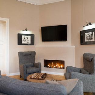 Diseño de sala de estar cerrada, rústica, pequeña, con paredes beige, suelo de madera en tonos medios, estufa de leña, marco de chimenea de yeso, televisor colgado en la pared y suelo marrón