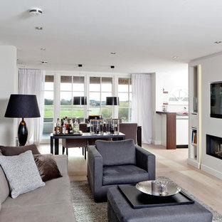 Klassisk inredning av ett mellanstort allrum med öppen planlösning, med vita väggar, ljust trägolv, en bred öppen spis, en spiselkrans i gips, en väggmonterad TV och en hemmabar