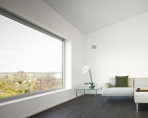 graues Ecksofa, weißes Regalsystem und Holzbodenbelag