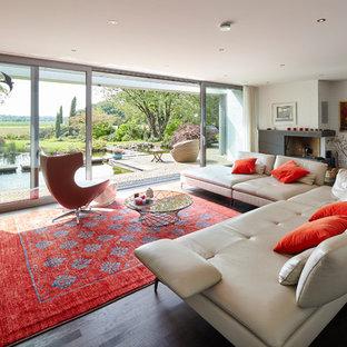 Großes, Repräsentatives, Offenes Modernes Wohnzimmer mit weißer Wandfarbe, gebeiztem Holzboden, Eckkamin und braunem Boden in Düsseldorf