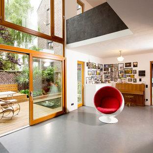 Trendy Concrete Floor And Gray Floor Living Room Photo In Essen With White  Walls