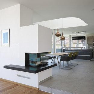 大きいコンテンポラリースタイルのおしゃれなファミリールーム (白い壁、両方向型暖炉、漆喰の暖炉まわり、テレビなし) の写真