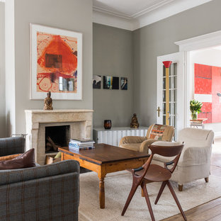 Example of a mid-sized classic enclosed painted wood floor and brown floor living room design in Hamburg with gray walls, a standard fireplace, a stone fireplace and a media wall