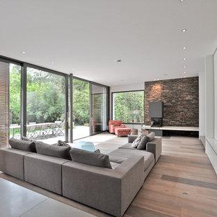 Immagine di un grande soggiorno contemporaneo aperto con pavimento in legno verniciato e TV a parete