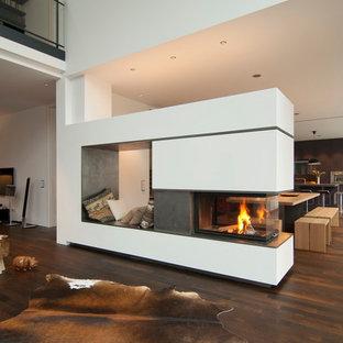 Foto de salón para visitas abierto, actual, grande, con paredes blancas, suelo de madera oscura, marco de chimenea de hormigón y chimenea de doble cara