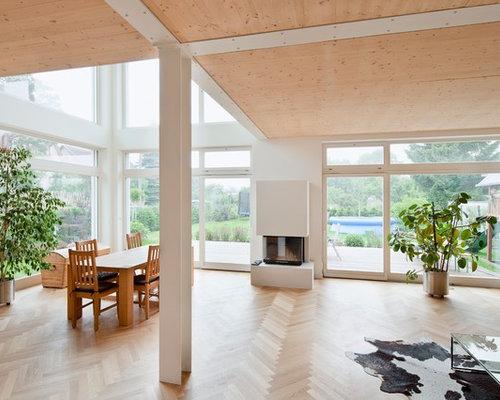 Gerumiges Offenes Nordisches Wohnzimmer Mit Weisser Wandfarbe Hellem Holzboden Kamin Und Verputztem Kaminsims