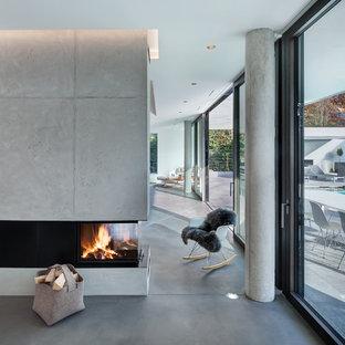 Exemple d'un très grand salon mansardé ou avec mezzanine moderne avec une salle de réception, un mur blanc, un sol en linoléum, une cheminée double-face, un manteau de cheminée en béton, aucun téléviseur et un sol gris.