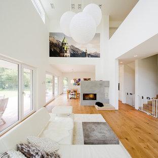 デュッセルドルフの大きいモダンスタイルのおしゃれなファミリールーム (白い壁、無垢フローリング、横長型暖炉、コンクリートの暖炉まわり) の写真