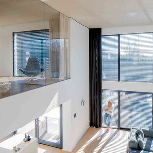 Esempio di un grande soggiorno minimalista stile loft con pareti bianche, pavimento in legno massello medio, camino ad angolo, cornice del camino in metallo, nessuna TV e pavimento beige