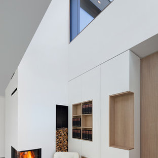 Idee per un piccolo soggiorno minimalista aperto con pareti bianche, pavimento in pietra calcarea, camino ad angolo e cornice del camino in intonaco