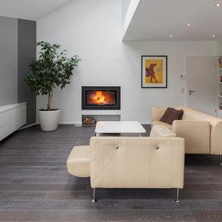 Mittelgroße, Offene Moderne Bibliothek mit weißer Wandfarbe, dunklem Holzboden, Kamin, Wand-TV, verputzter Kaminumrandung und braunem Boden in Köln