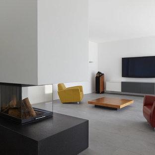Immagine di un grande soggiorno contemporaneo chiuso con camino bifacciale, pareti bianche, pavimento in ardesia, cornice del camino in pietra e TV a parete