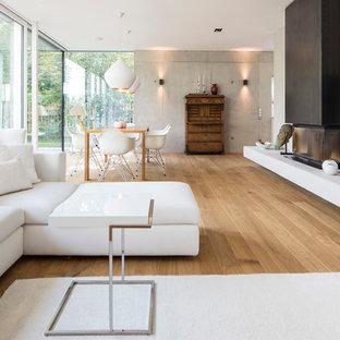 Ispirazione per un grande soggiorno moderno aperto con pareti grigie, pavimento in legno verniciato, camino bifacciale e TV a parete