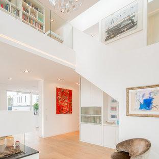 Großes, Offenes, Repräsentatives Modernes Wohnzimmer mit weißer Wandfarbe, braunem Holzboden, Gaskamin, verputzter Kaminumrandung, Multimediawand und beigem Boden in Düsseldorf