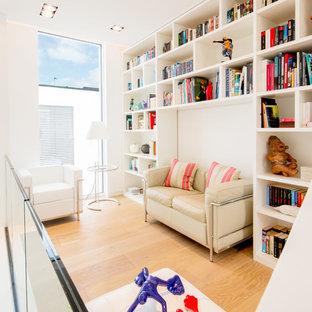 Offene, Kleine Moderne Bibliothek ohne Kamin mit weißer Wandfarbe, braunem Holzboden und beigem Boden in Düsseldorf