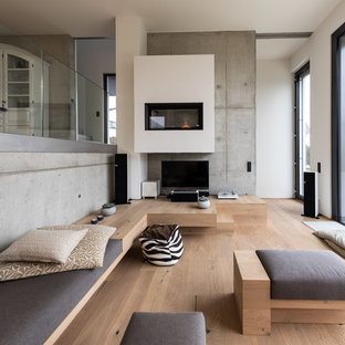 Ispirazione per un ampio soggiorno minimal stile loft con sala formale, camino sospeso, cornice del camino in intonaco, TV autoportante, pareti marroni, parquet chiaro e pavimento marrone
