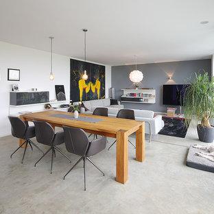 Mittelgroßes, Repräsentatives, Offenes Modernes Wohnzimmer ohne Kamin mit weißer Wandfarbe, Betonboden, Wand-TV und grauem Boden in München