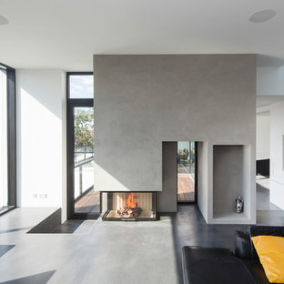 Family room - large contemporary open concept gray floor and concrete floor family room idea in Stuttgart with white walls, a wood stove, a plaster fireplace and no tv