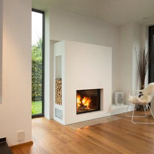 Imagen de sala de estar con biblioteca abierta, actual, grande, sin televisor, con paredes grises, suelo de madera clara, estufa de leña, marco de chimenea de yeso y suelo beige
