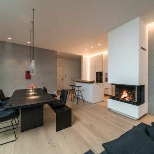 Großes, Repräsentatives, Offenes, Fernseherloses Modernes Wohnzimmer mit grauer Wandfarbe, braunem Holzboden, Kamin, verputzter Kaminumrandung und braunem Boden in Stuttgart
