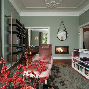 Großes, Repräsentatives, Offenes, Fernseherloses Klassisches Wohnzimmer mit Tunnelkamin, verputztem Kaminsims, grüner Wandfarbe, braunem Holzboden und braunem Boden in Stuttgart
