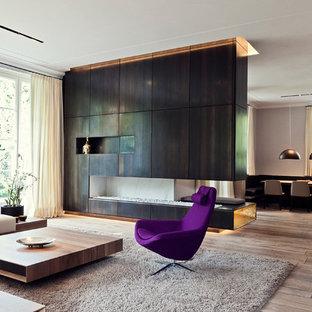 Imagen de salón abierto, actual, grande, con suelo de madera en tonos medios, chimeneas suspendidas, marco de chimenea de metal, televisor retractable y paredes beige