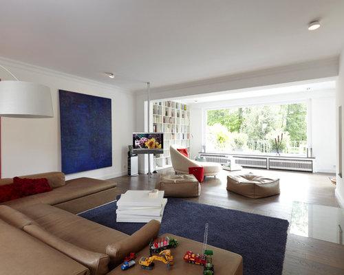 Großes, Offenes Modernes Wohnzimmer Mit Weißer Wandfarbe, Dunklem  Holzboden, Verputztem Kaminsims, Freistehendem
