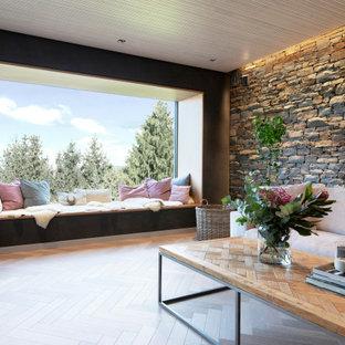 他の地域の広いインダストリアルスタイルのおしゃれなオープンリビング (黒い壁、淡色無垢フローリング、両方向型暖炉、金属の暖炉まわり、ベージュの床) の写真