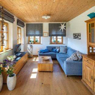 Country Wohnzimmer mit weißer Wandfarbe, braunem Holzboden, braunem Boden und Holzdecke in München