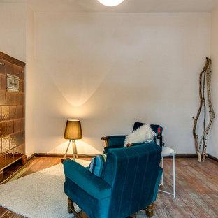 Kleines, Fernseherloses, Abgetrenntes Stilmix Wohnzimmer mit weißer Wandfarbe, braunem Holzboden, Kaminofen, gefliester Kaminumrandung und braunem Boden in Bremen