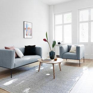 Abgetrenntes Skandinavisches Wohnzimmer mit weißer Wandfarbe, hellem Holzboden und beigem Boden in Berlin