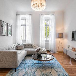 Abgetrenntes Modernes Wohnzimmer mit weißer Wandfarbe, braunem Holzboden, Wand-TV und braunem Boden in Dresden