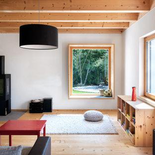 Mittelgroßes, Fernseherloses Asiatisches Wohnzimmer mit weißer Wandfarbe, hellem Holzboden, Kaminofen, Kaminumrandung aus Metall und beigem Boden in München